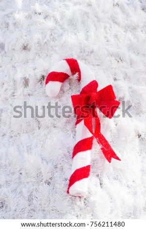 Christmas candy cane decoration with red bow on artificial white fir needle background. xmas, new year, winter holidays celebration concept