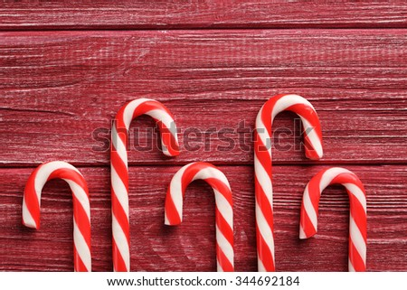 Christmas candy cane on a red wooden table - stock photo