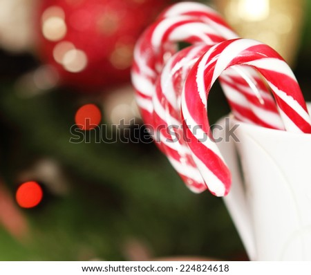 Christmas Candy Canes by the Christmas tree. Toned shot - stock photo