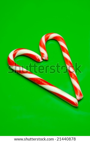 Christmas candy canes isolated against a green background