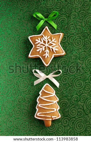 Christmas card background. Ginger and Honey cookies in the shape of a Christmas fir tree and snowflake with white sugar decoration and bows on the green paper background. - stock photo