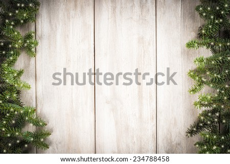 Christmas card background with a space for text on a wooden surface and decorated with fir branches - stock photo
