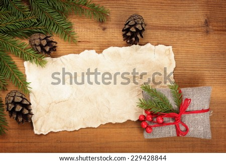 Christmas card: blank, vintage rural gift and Christmas tree branch on wooden background - stock photo