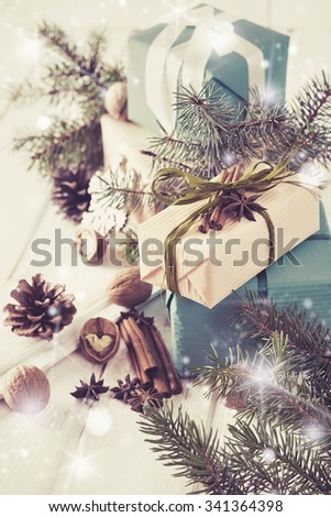 Christmas Card.Christmas Boxes, Coniferous, Pine Cones, Nuts and Bunch of Cinnamon  on Lighten Wooden Background.Selective focus.