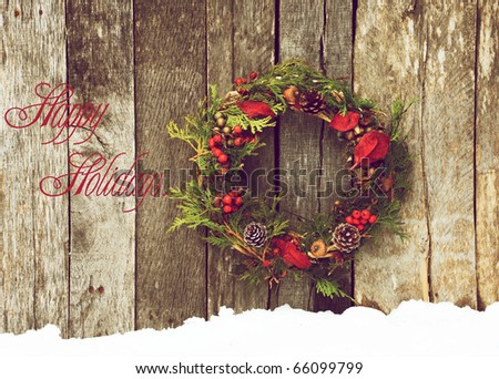 Christmas card design featuring a Christmas wreath with natural decorations hanging on a rustic wooden wall with snow and copy space. - stock photo