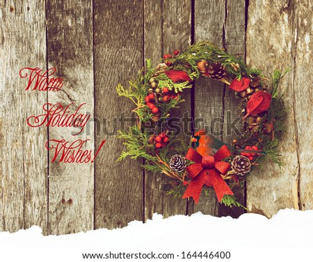 Christmas card design with a beautiful male northern cardinal perched in a rustic wreath hanging on a wooden background, with text-Warm Holiday Wishes! - stock photo