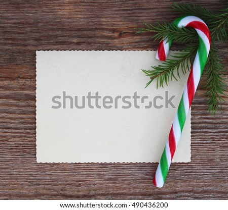 Christmas card: empty paper form and candy cane with fir-tree branches on old wooden background