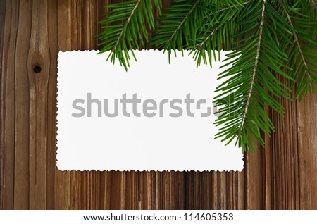 Christmas card: empty paper form with fir-tree branches on old wooden background