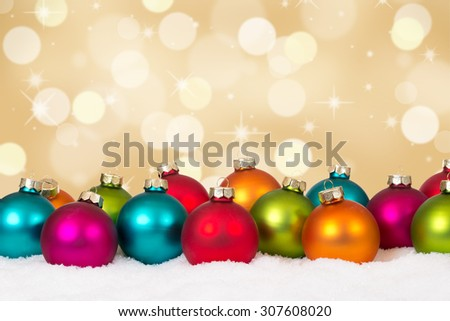 Christmas card many colorful balls golden background decoration with copyspace and snow