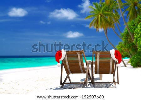 Christmas card or background - two sunloungers with Santa hats standing on beautiful tropical beach with palm trees, white sand and turquoise water on Maldives. Concept of perfect vacation.  - stock photo
