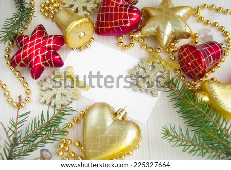 Christmas card surrounded by decorations on wooden background