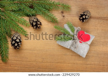 Christmas card. Vintage rural gift  and Christmas tree branch on wooden background - stock photo