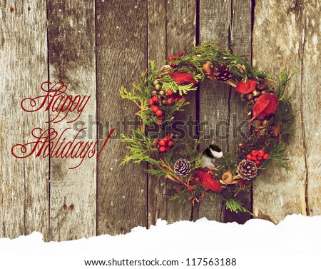 Christmas card with a pretty wreath and chickadee in the snow with text-Happy Holidays! - stock photo