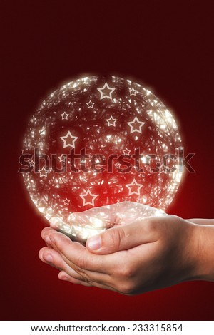 Christmas card with a shiny ball coming from a child hands on a red background, a traditional gift that Christians people use tu send their friends to congratulate them in Christmas time - stock photo