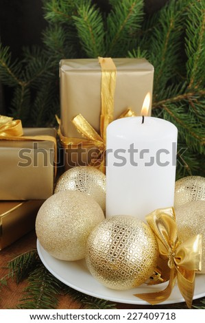 Christmas Card with decorations on texture wooden background. White candle, gift boxes with presents,  xmas tree and color balls.  - stock photo