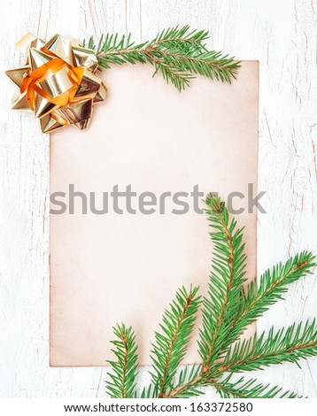 Christmas card with golden bow and fir branches - stock photo