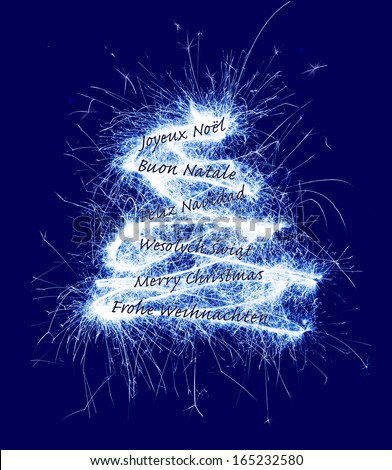 Christmas card with greetings in six different languages. Christmas tree made with real sparklers on dark blue. - stock photo