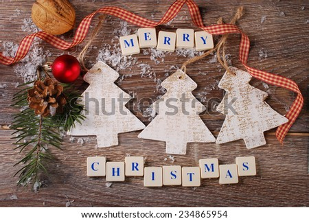 christmas card with greetings made of  letter cubes with  three wooden christmas trees  - stock photo