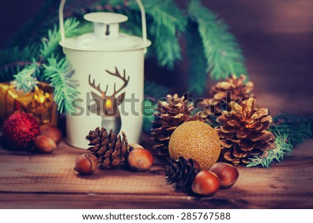 Christmas card with lantern, candle, fir tree, x-mas decorations, nuts and cones. Toned image, selective focus - stock photo