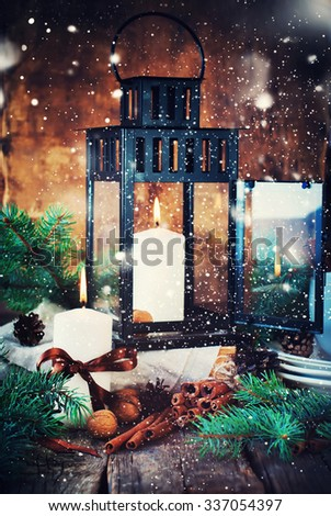 Christmas Card with Lantern. Festive Dishware, Candles, Cinnamons, Pine cones, WalnutsFir Tree on the Wooden Table in Festive Composition. Effect Drawn Snow