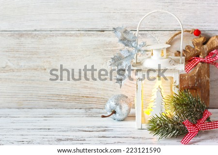 Christmas card with lantern, fir branch and wooden deer. - stock photo