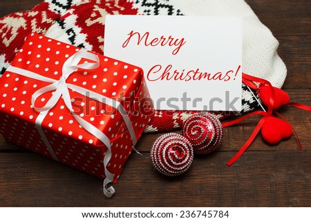 Christmas Card with Message Merry Christmas on the letter ,composition with Gift, Sweater and christmas toys on wooden table - stock photo