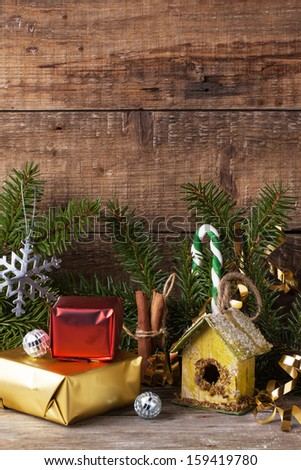 Christmas card with nesting box and christmas gifts over old wooden background