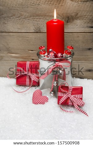 Christmas card with red candles, presents red and white checked and decoration, snow on wooden background  - stock photo