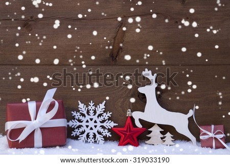 Christmas Card With Red Festive Decoration On White Snow. Gift, Present, Reindeer, Christmas Ball, Christmas Tree, Snowflakes. Brown, Rustic, Vintage Wooden Background. Copy Space For Advertisement - stock photo