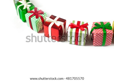 Christmas card with red, green and gold gifts on white table. Little Christmas gifts. A lot of Christmas presents.