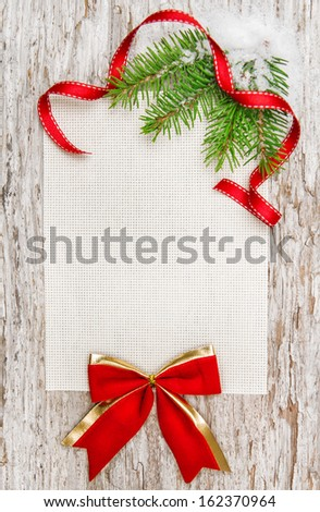 Christmas card with red ribbon, bow and fir branch on the old wood - stock photo