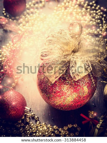 Christmas card with red vintage bauble, golden ribbon and  decoration on sparkle holiday background - stock photo
