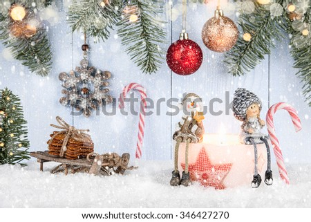 Christmas card with smiling figurines, candle, cookies and other Christmas decor - stock photo