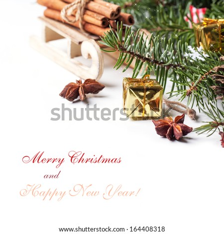 Christmas card with wooden sled with heap of cinnamon and golden gift box over white with sample text - stock photo