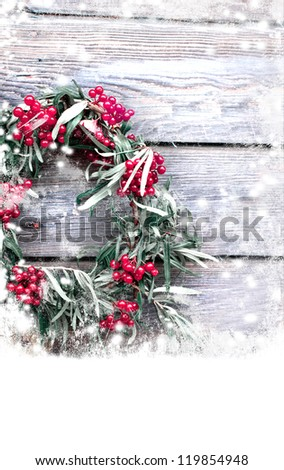 Christmas card with wreath from red berry  on a rustic wooden wall with copy space with a snow/holidays background - stock photo