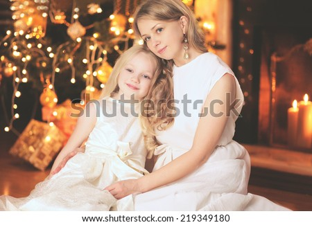 Christmas, celebration and people concept - happy mother and child near christmas tree and fireplace - stock photo