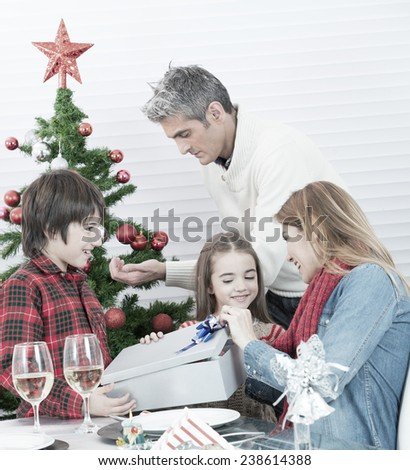 Christmas celebration at home. Family with 2 children at the table unwrapping gifts. - stock photo