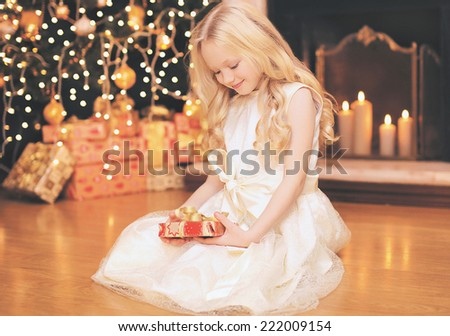 Christmas, celebration, holiday, xmas concept - happy little girl with gifts near christmas tree and fireplace - stock photo