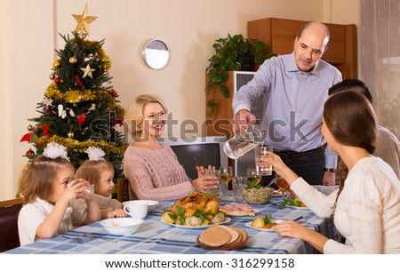 Christmas celebration in the bosom of smiling family at the table at home