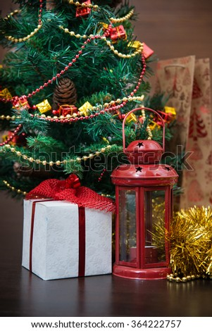 Christmas celebration things: firtree with gifts under it, decoration, garlands in warm interior