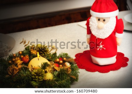 Christmas centerpiece with candle and bottle as Santa Claus. - stock photo