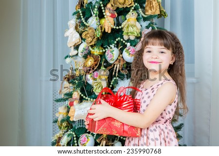 Christmas. Cheerful little girl holding a gift box and smiling - stock photo