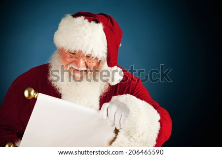 Christmas: Cheerful Santa Claus Reading the Naughty and Nice List - stock photo