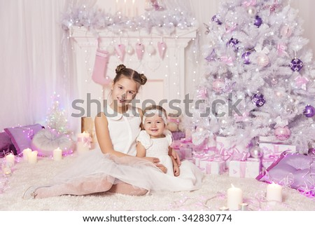 Christmas Children, Kid and Baby Girls with Present Gift, Decorated Pink Room Xmas Tree - stock photo