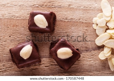 Christmas chocolate sweets covered by nuts on wooden background