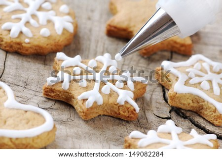 Christmas cinnamon cookies icing decorating process with a pastry bag - stock photo