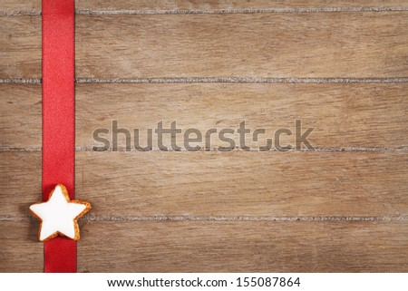 christmas cinnamon star on a red ribbon on vintage wooden background with copyspace - stock photo