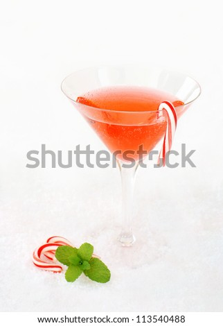 Christmas cocktail decorated with candy canes and a mint leaf. - stock photo