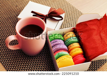 Christmas coffee break with gift box and macaroons with a retro vintage instagram filter. - stock photo