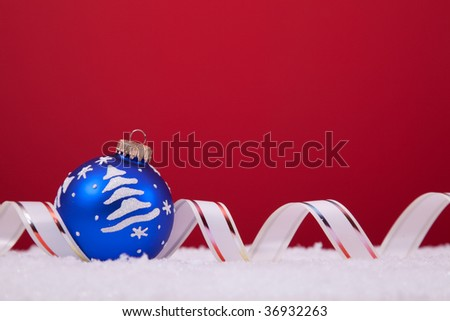 christmas colorful balls over the snow with a red background (selective focus)